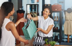small business owner handing bag to customer
