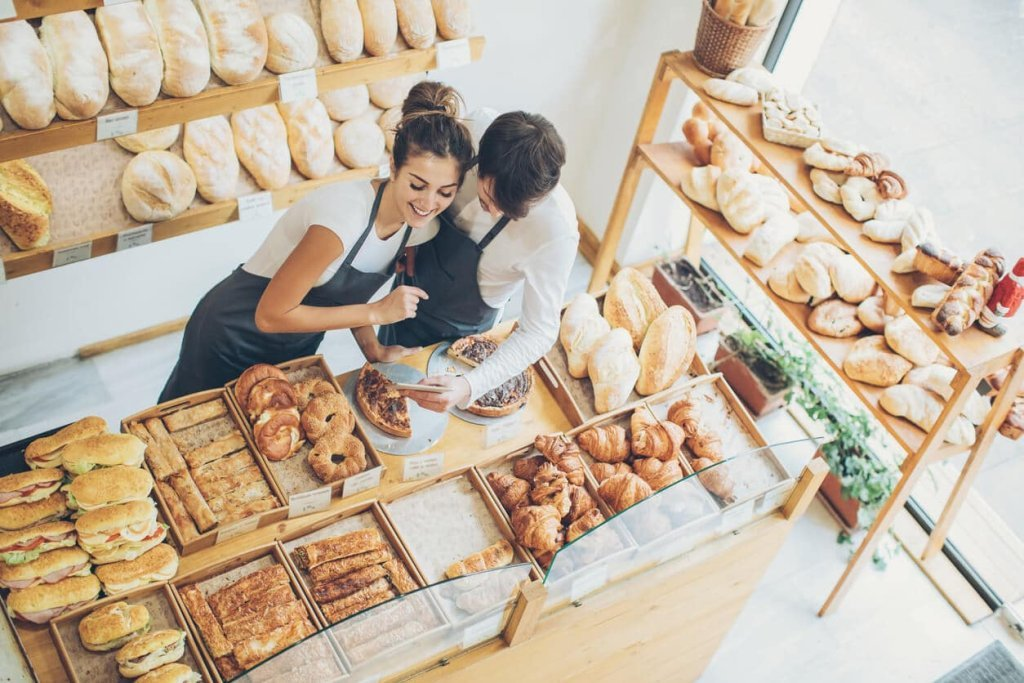 Couple surrounded by displays in their bakery
