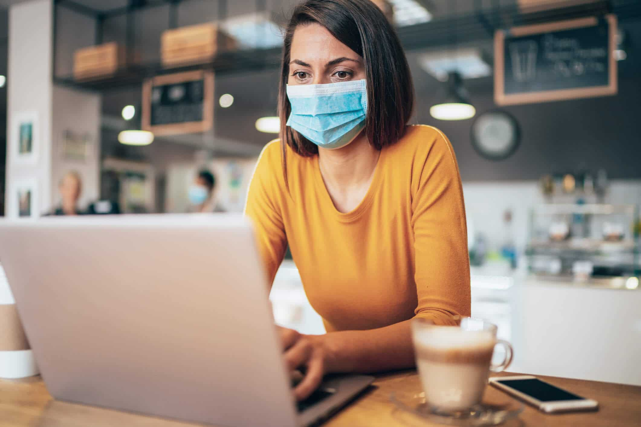 Small business owner wearing a medical mask and working on computer