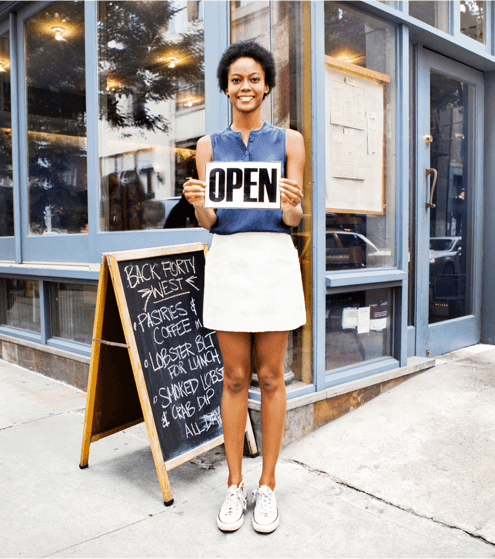 Women holding open sign in front of business